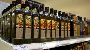 Flaskor med olivolja på butikshyllan.