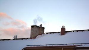 Ett snötäckt tak med en skorsten varifrån det kommer rök.