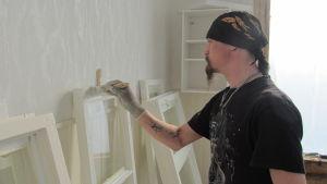 Arbetslöse Niklas Karlberg restaurerar fönster på folkhögskolan i Hangö