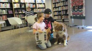 Taida och Brandon läser med hunden Martta
