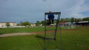 Eino Fredriksson sitter på en ställning för att se fotbollsmatchen bra då han syntolkar. Det är ganska svårt att se bortre planen.