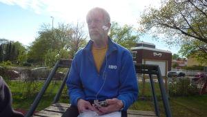 Eino Fredriksson sitter på en ställning för att se fotbollsmatchen bra då han syntolkar.