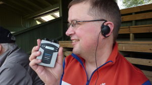Jan-Peter Sjöholm visar apparaten som gör att han hör syntolkningen.