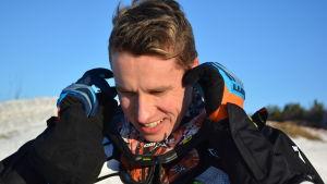 Viktor Hertén skyddar öronen innan han startar sin snöskoter.