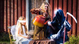 ett barn utklädd till ängel sitter vid ett bord och dricker te tillsammans med liemannen. En gumma serverar ur en stor kanna