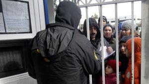 Flyktingar utanför migrationsmyndigheten i Athen för att söka asyl.