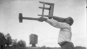 En man lyfter en stol vågrätt med sina bara tänder, samt en slägga med sin arm, samtidigt. Bilden är tagen 1931 i Närpes, Kalaks.