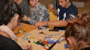 Studerande från olika länder gör armband på seminarium vid Källhagens skola i Virkby.