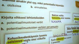äidinkielen potentiaalimuotoja käsittelevä dia seinällä