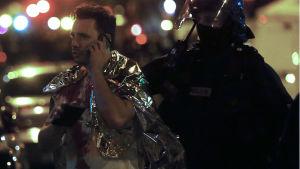 Polisen evakuerar en man från Bataclan.