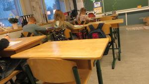 Lågstadie elever som sitter och skriver
