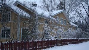 gult trähus  i vinterskrud. Huset finns i Bromarv och fungerade i tiderna som matbutik.