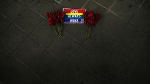 """En liten regnbågsflagga med texten """"Kärleken vinner alltid"""" tillsammans med två röda blombuketter utanför USA:s ambassad i Bangkok, Thailand."""