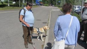 Kenneth Ekholm och hans ledarhund Assar testar trottoarkanterna vid Nickby hälsovårdscentral
