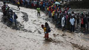 Människor försöker ta sig över floden La Digue i sydvästra Haiti.