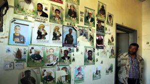 En vägg med bilder på offren för flygräden mot begravningslokalen i Sanaa
