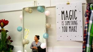 affisch och en spegel där en kvinna syns i bakgrunden