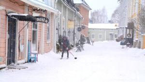 En kvinna sopar bort snön utanför sin affär i Borgås Gamla stan.