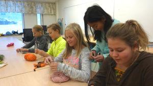 Victoria Alopaeus, Edvin Karell, Alma Krogell, Annie Keskinen och Ronja Heinström handarbetar vid ett bord i Sjundeå svenska skola.