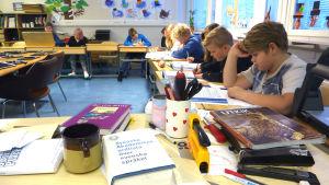 Elever sitter vid sina skolbänkar och läser i Degerby skola i ingå.