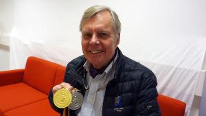 Nils-Gustav Höglund sitter i en soffa med två OS-medaljer i handen.