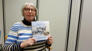 Gun Holm håller i en bok i lokalhistoria som hon varit med och skrivit.