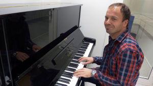 Kristoffer Holmberg sitter och spelar piano.