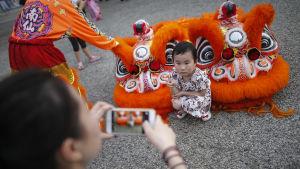 En liten flicka poserar vid en lejonkostym i Singapore.