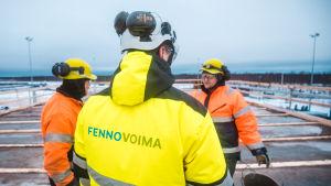 Tre män i grälla arbetskläder på Fennovoimas bygge.