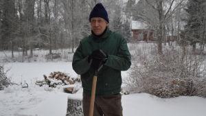 En man står lutad mot en snöskyffel med snöig bakgrund. Han heter Gösta Lundén.
