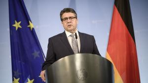 Sigmar Gabriel, Tysklands utrikesminister står mellan EU:s och Tysklands flaggor.