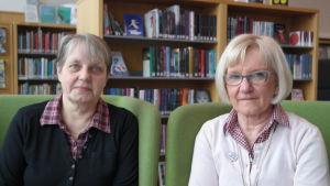 Gunilla Ritkaew och Anne Lindroos sitter i gröna fåtöljer i biblioteket i Villa Lande i Kimito
