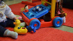 Två spädbarn leker med leksaker på en röd matta.