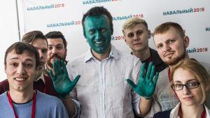 Oppositionsledaren Aleksej Navalnyj i sitt kampanjhögkvarter omgärdad av medarbetare. Navalnyj har målat sitt ansikte grönt som en pik mot angripare som slängde en grön vätska på honom nyilgen