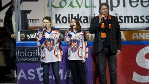 Pentti Hietanen med döttrarna Iina och Roosa framför nationalsången på ligafinal fem.