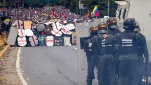Polis med kravallsköldar och vattenkanoner står mittemot tusentals demonstranter som söker skydd bakom fanersköldar på en motorväg i Caracas.
