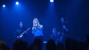 Chromatics på scenen i blått ljus.