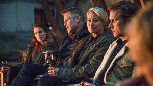 Några av karaktärerna i serien Arvingarna äter utomhus framför öppen eld i mörkret.