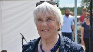 äldre dam med vitt grått hår och solglasögon står under ett tält på de vita pärons potatisfestival i nagu.