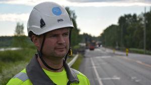 Ulf Granholm i porträtt. Han bär hjälm och arbetskläder. I bakgrunden ser man vägarbetet på riksåttan ur fokus.