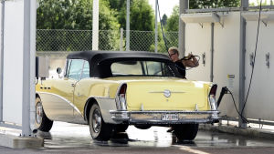En man tvättar bilen vid ett ställe ämnat för biltvätt.