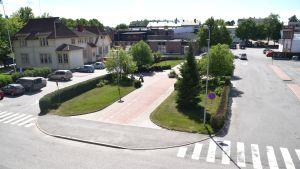 Ett gammalt hus, en liten grön park och bussperronger