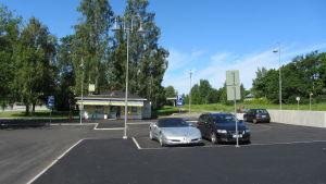 En parkering där några bilar står parkerade. I bakgrunden syns en kiosk.