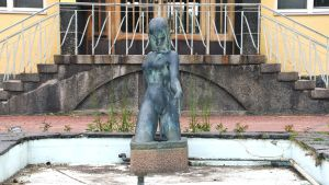 En staty, kvinnlig figur, i en liten ljusblå bassäng utan vatten, sand och löv och vattenrör syns på bassängbottnen.
