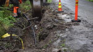 En grävskopa som gräver ett dike. Gult band ovanför jordkabeln visar att det finns en kabel om någon börjar gräva.