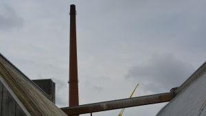 På bilden ser man skorstenen på avstånd mellan två sädessilon. Bredvid skorstenen står en gul lyftkran.