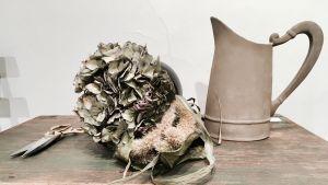 Ett slitet träbord med en kanna, torkade hortensior och en sax i guld.