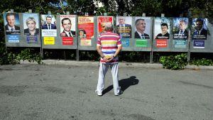 En man tittar på valaffischer i Saint-André-de-la-Roche, nära Nice den 10 april 2017 inför det franska presidentvalet.