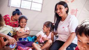 Gita Subedi, som är en av Nepal Röda Kors frivilliga inom psykosocialt stöd delar ut vatten åt barn