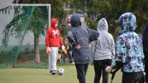 Vårberga skolas elever spelar fotboll i en hagelskur.
